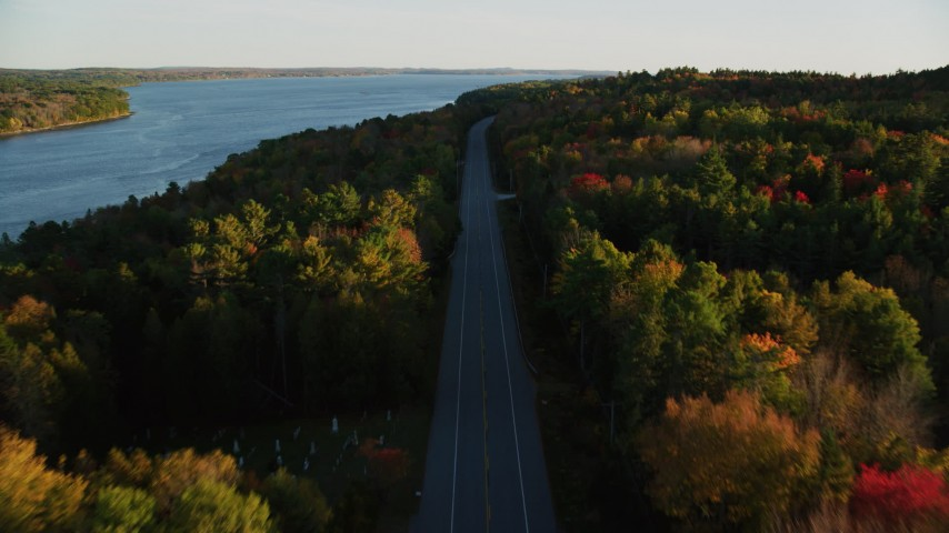 6K stock footage aerial video flying over quiet road among a colorful forest in autumn, Stockton Springs, Maine, sunset Aerial Stock Footage | AX149_120