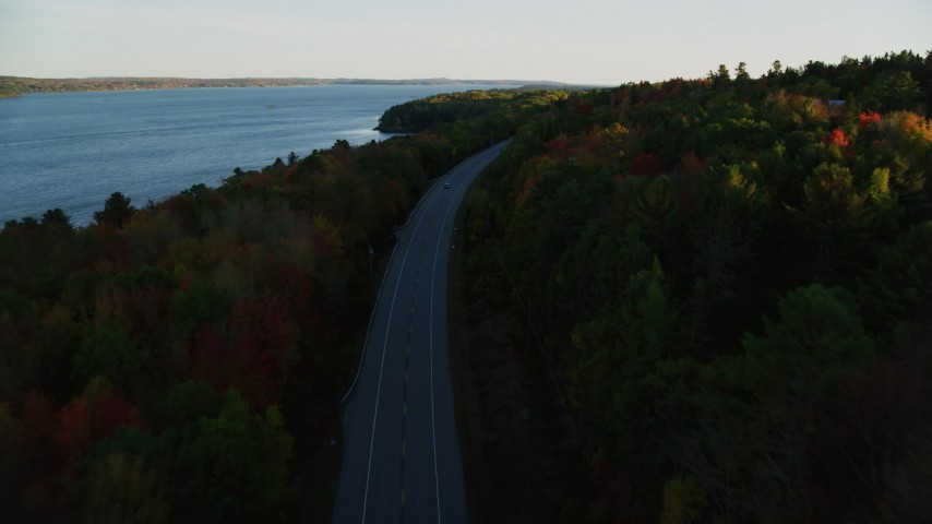 6K stock footage aerial video flying over road with no traffic, colorful forest in autumn, Stockton Springs, Maine, sunset Aerial Stock Footage | AX149_121