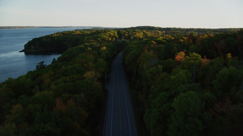 6K aerial video flying over a road situated among, colorful forest in autumn, Stockton Springs, Maine, sunset Aerial Stock Footage | AX149_122