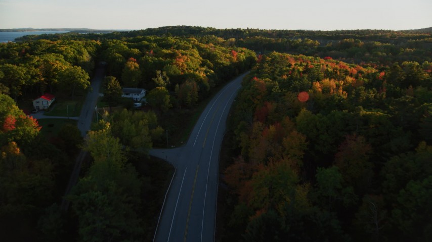 6K aerial video flying over road and tilt down, light traffic, colorful forest in autumn, Stockton Springs, Maine, sunset Aerial Stock Footage | AX149_123