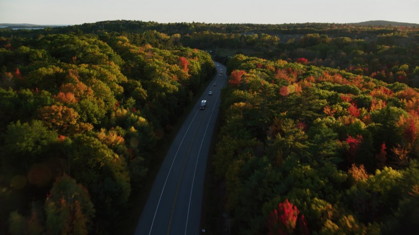 6K aerial video flying over forest road with light traffic, fall foliage, in autumn, Stockton Springs, Maine, sunset Aerial Stock Footage | AX149_124