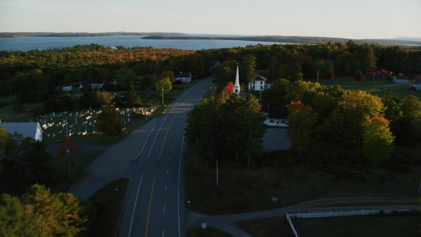 6K stock footage aerial video flying over road, church and cemetery, autumn, Stockton Springs, Maine, sunset Aerial Stock Footage | AX149_127