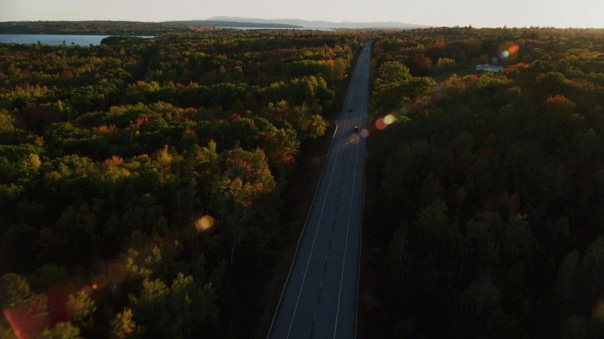 6K stock footage aerial video tracking car on road through forest, autumn, Stockton Springs, Maine, sunset Aerial Stock Footage | AX149_129