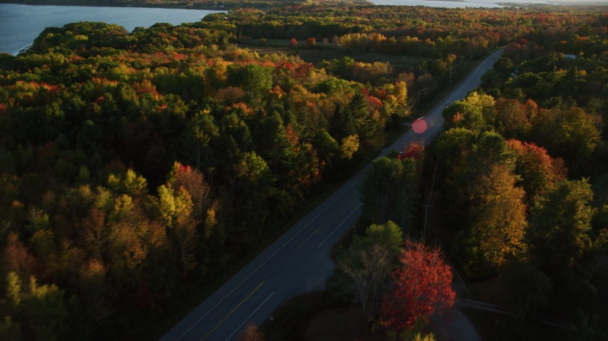6K stock footage aerial video tracking car on road through forest, autumn, Stockton Springs, Maine, sunset Aerial Stock Footage | AX149_131