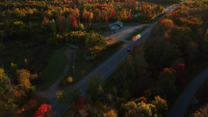 6K stock footage aerial video tracking car on road through forest in autumn, Stockton Springs, Maine, sunset Aerial Stock Footage | AX149_133