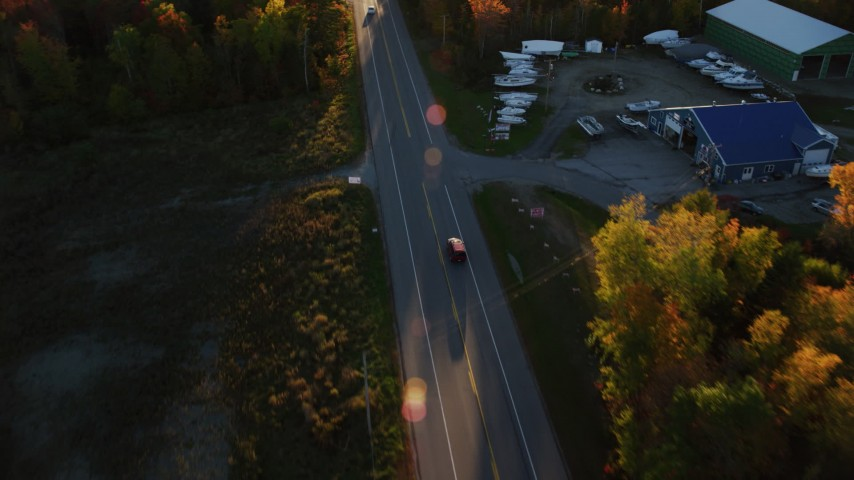 6K stock footage aerial video tracking car on road through forest in autumn, Stockton Springs, Maine, sunset Aerial Stock Footage | AX149_134