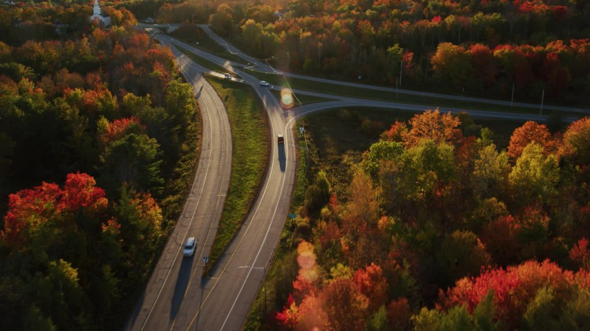 6K aerial video of a car on road approaching a church, autumn, Stockton Springs, Maine, sunset Aerial Stock Footage | AX149_136