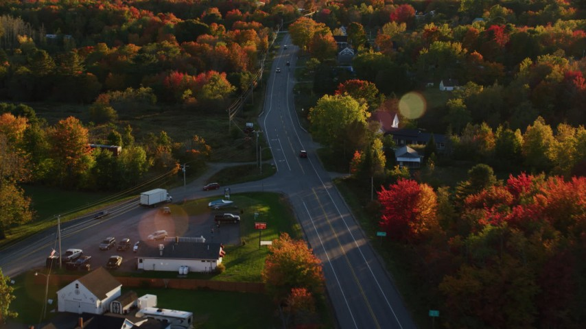 6K stock footage aerial video tracking car on road with light traffic, through small town, autumn, Stockton Springs, Maine, sunset Aerial Stock Footage | AX149_140