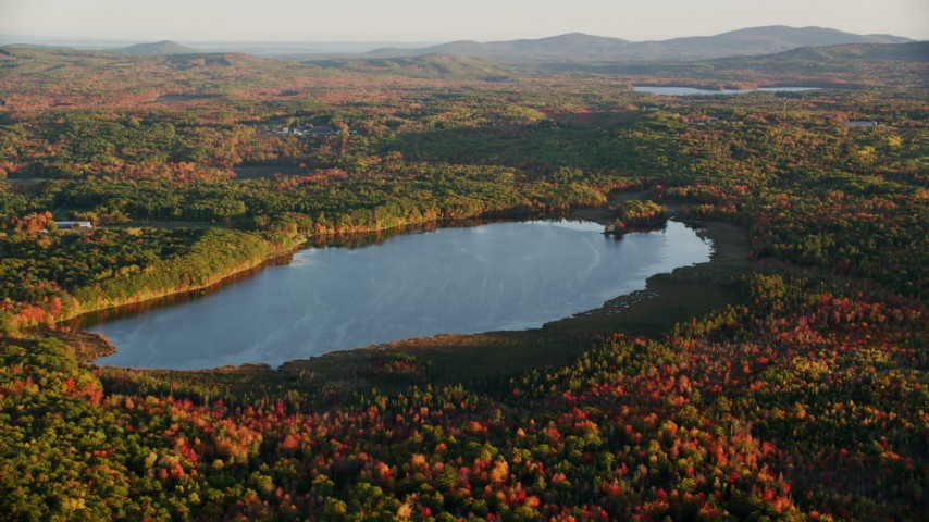 6K stock footage aerial video flying by Cross Pond, forest in autumn, Belmont, Maine, sunset Aerial Stock Footage | AX149_167