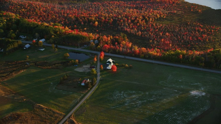 6K stock footage aerial video approaching a rural home near Route 3, forest in autumn, Belmont, Maine, sunset Aerial Stock Footage | AX149_170