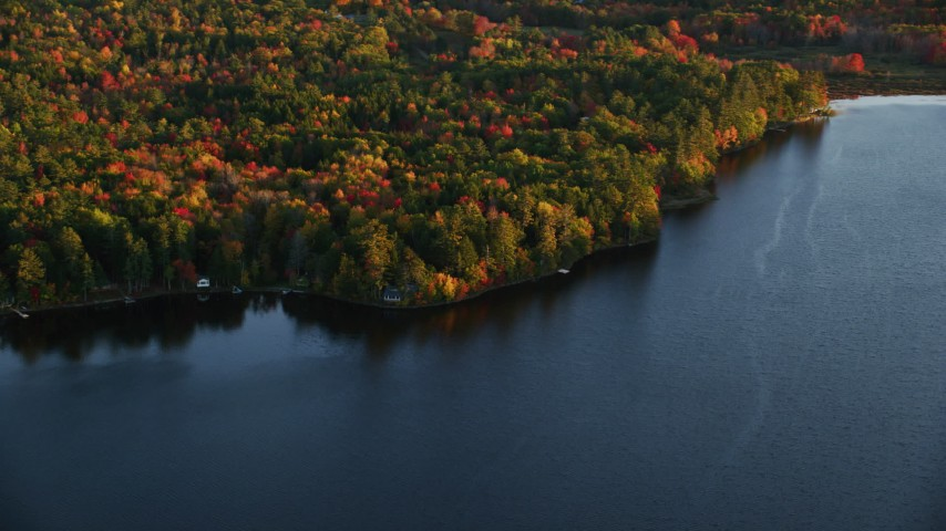6K aerial video flying by homes on Quantabacook Lake, forest in autumn, Searsmont, Maine, sunset Aerial Stock Footage | AX149_173