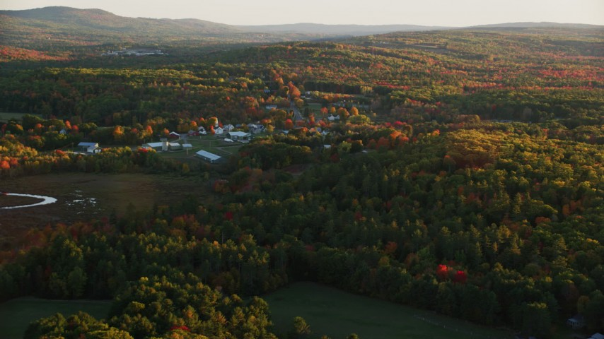 6K aerial video approaching small rural town, colorful trees in autumn, Searsmont, Maine, sunset Aerial Stock Footage | AX149_174