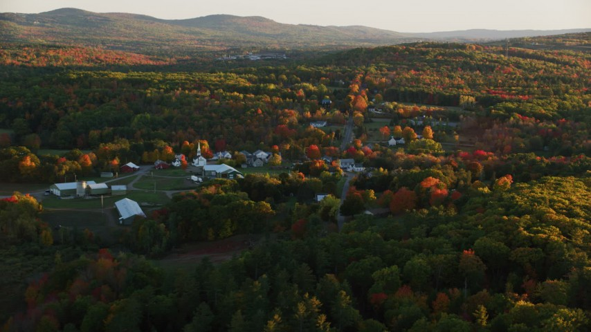 6K aerial video approaching small rural town, colorful forest in autumn, Searsmont, Maine, sunset Aerial Stock Footage | AX149_175
