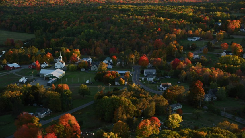 6K aerial video flying by small rural town, colorful forest in autumn, Searsmont, Maine, sunset Aerial Stock Footage | AX149_176