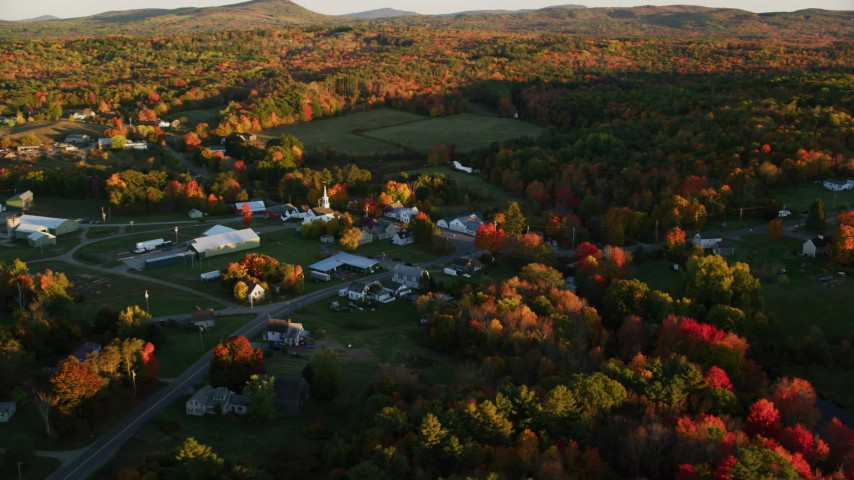 6K aerial video orbiting small rural town near colorful forest, autumn, Searsmont, Maine, sunset Aerial Stock Footage AX149_177