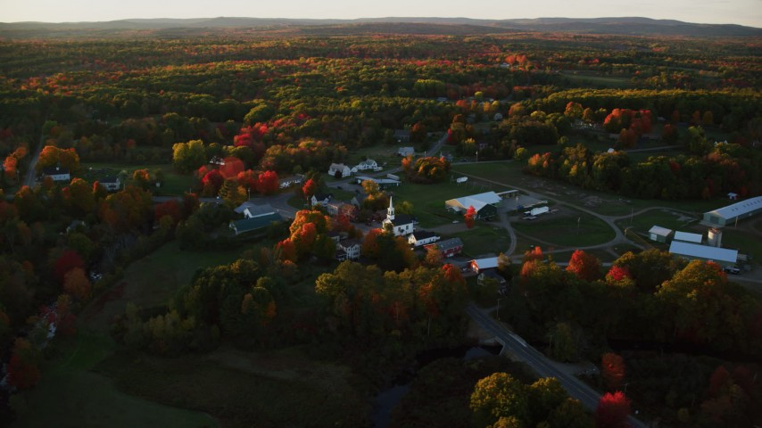 6K aerial video orbiting a small rural town and trees in autumn, Searsmont, Maine, sunset Aerial Stock Footage | AX149_180
