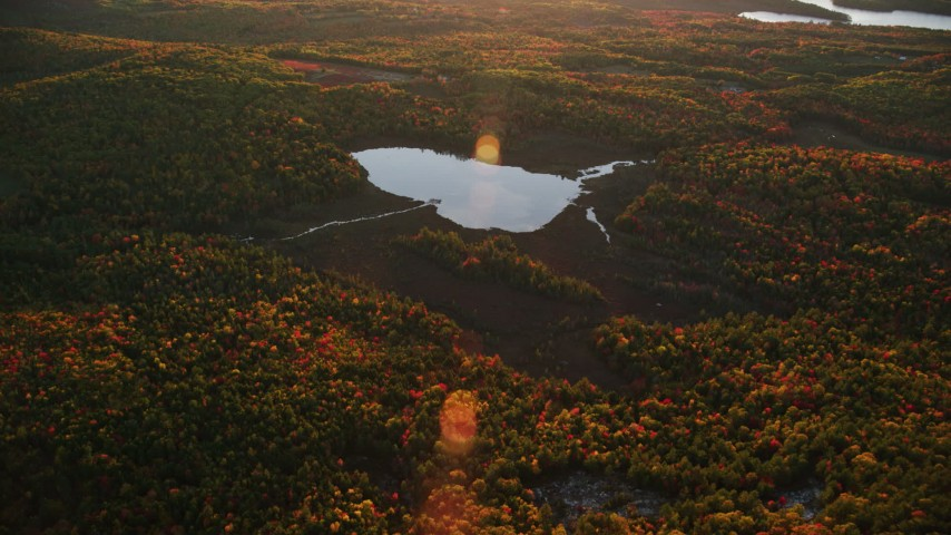 6K stock footage aerial video approaching Colby Pond, tilt down, autumn, Palermo, Maine, sunset Aerial Stock Footage | AX149_194