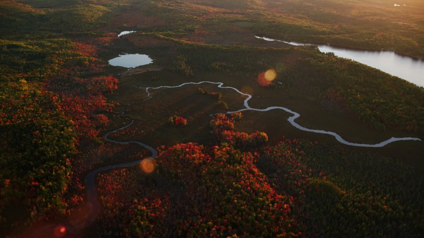 6K stock footage aerial video flying by rivers near pond, colorful forest in autumn, Palermo, Maine, sunset Aerial Stock Footage | AX149_197