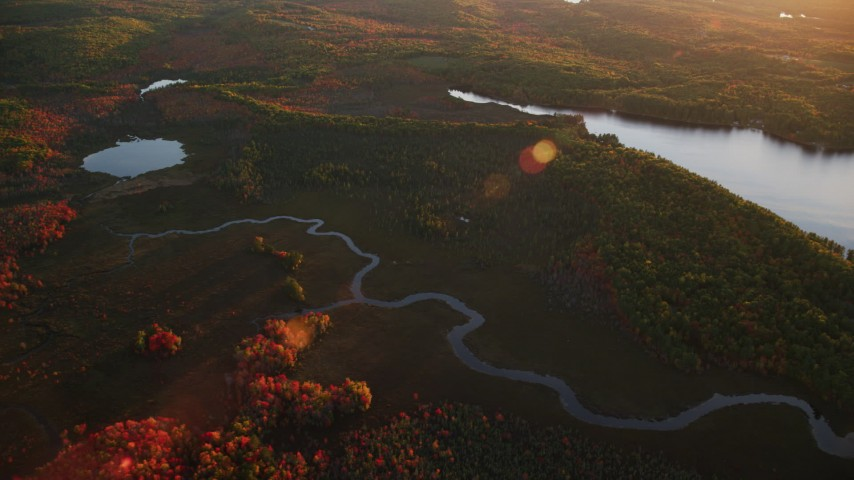 6K stock footage aerial video flying by river, pond, and colorful forest in autumn, Palermo, Maine, sunset Aerial Stock Footage AX149_198