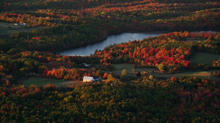 6K stock footage aerial video flying by rural homes, forest and Beech Pond, autumn, Palermo, Maine, sunset Aerial Stock Footage | AX149_199