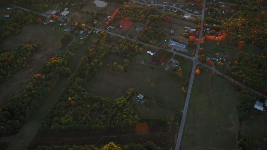 6K stock footage aerial video of a bird's eye view over rural homes and intersection, autumn, Augusta, Maine, sunset Aerial Stock Footage | AX149_213