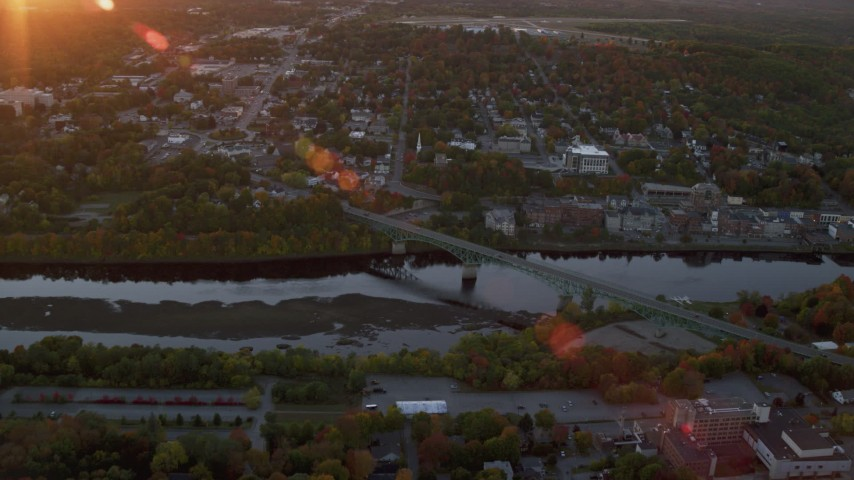 6K stock footage aerial video approaching downtown, small bridge, Kennebec River, autumn, Augusta, Maine, sunset Aerial Stock Footage | AX149_214