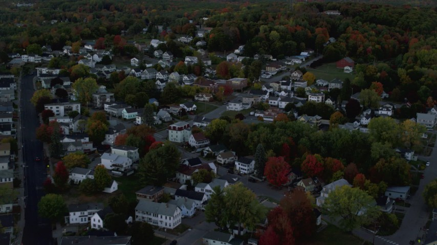 6K stock footage aerial video flying over neighborhood  and colorful foliage in autumn, Augusta, Maine, twilight Aerial Stock Footage AX149_238