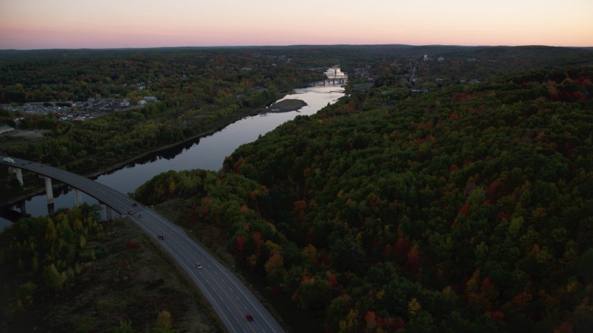 6K stock footage aerial video flying over forest in autumn, approach Kennebec River, Augusta, Maine, twilight Aerial Stock Footage | AX149_242