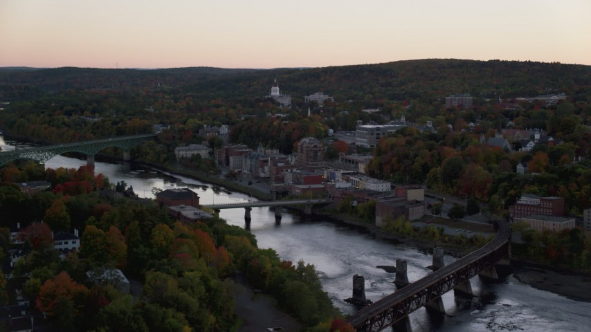 6K stock footage aerial video flying by small bridges on Kennebec River, downtown, autumn, Augusta, Maine, twilight Aerial Stock Footage | AX149_246