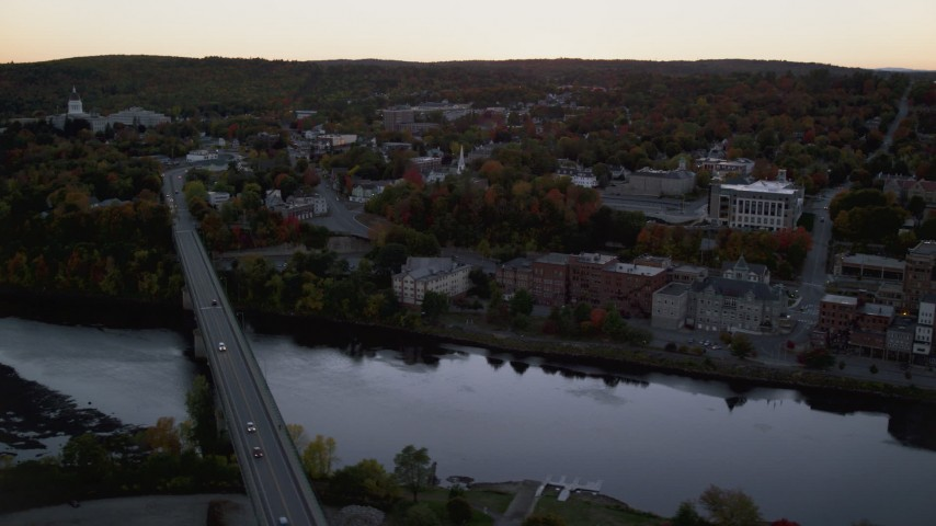 6K stock footage aerial video flying by small bridges into downtown, Kennebec River, Autumn, Augusta, Maine, twilight Aerial Stock Footage | AX149_248