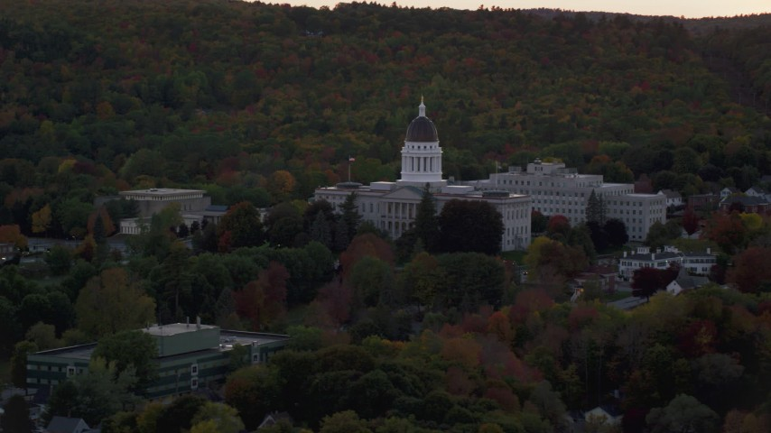 6K stock footage aerial video flying by the Maine State House, dense trees, autumn, Augusta, Maine, twilight Aerial Stock Footage AX149_249
