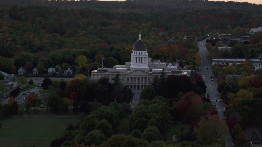 6K stock footage aerial video flying by dense trees surrounded Maine State House, autumn, Augusta, Maine, twilight Aerial Stock Footage | AX149_250