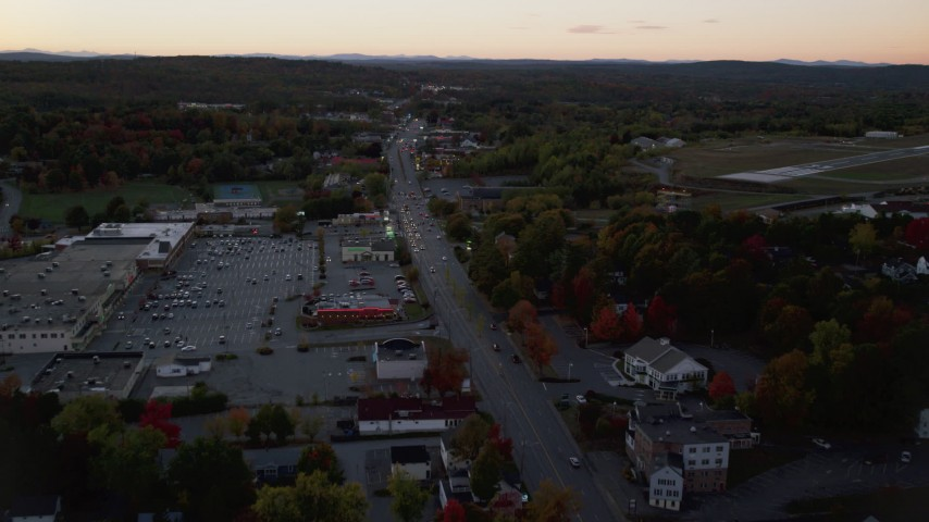 6K stock footage aerial video approaching Western Avenue strip mall in autumn, Augusta, Maine, twilight Aerial Stock Footage | AX149_254