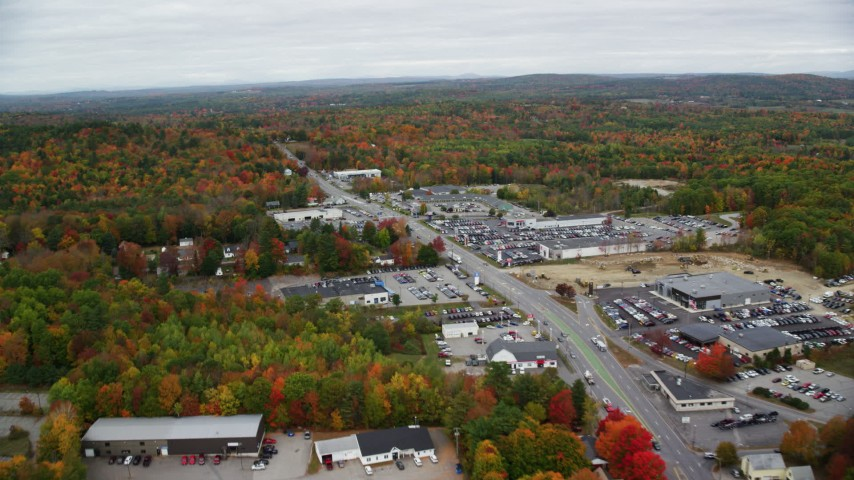 6K stock footage aerial video flying by car dealerships, Western Avenue, autumn, Augusta, Maine Aerial Stock Footage | AX150_001