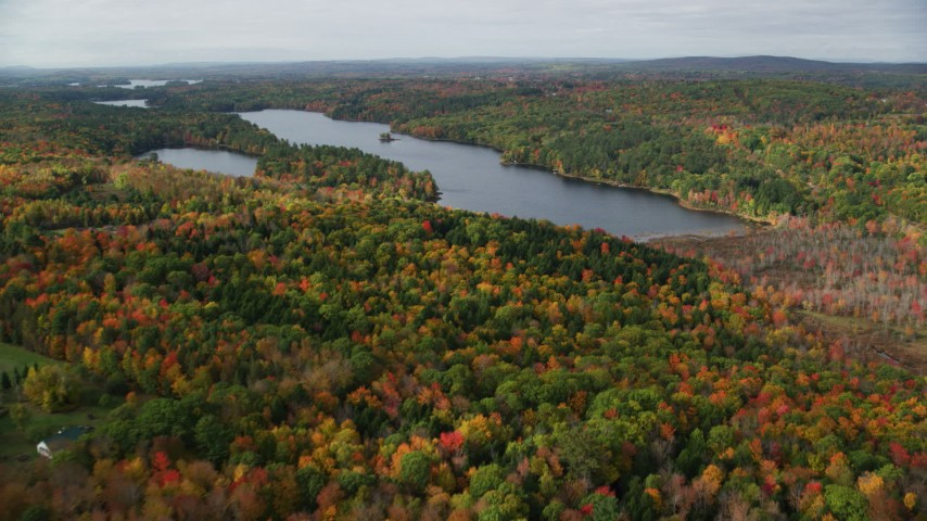 6K stock footage aerial video flying over colorful forest, approach Upper Narrows Pond, autumn, Winthrop, Maine Aerial Stock Footage | AX150_010