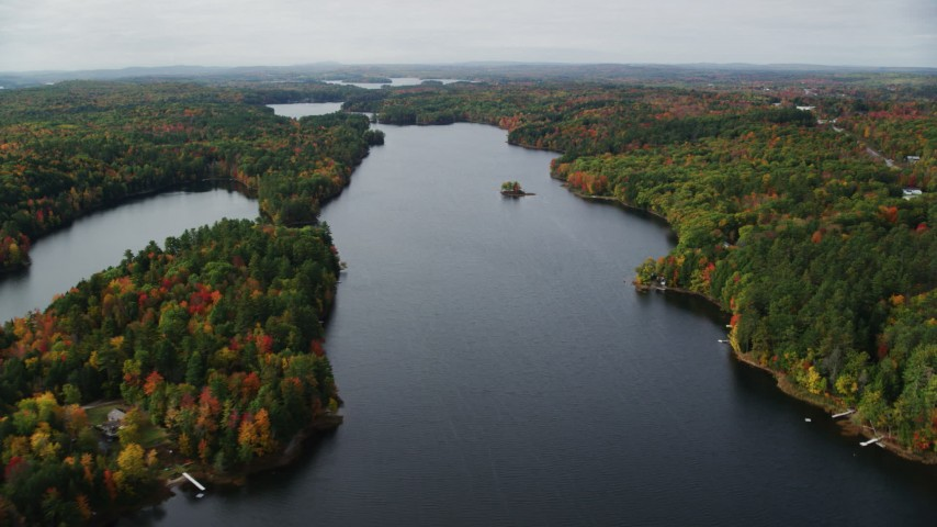 6K stock footage aerial video flying by Upper Narrows Pond, dense forest in autumn, Winthrop, Maine Aerial Stock Footage | AX150_011