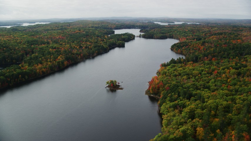 6K stock footage aerial video flying by Upper Narrows Pond, forest of colorful trees, autumn, Winthrop, Maine Aerial Stock Footage | AX150_012