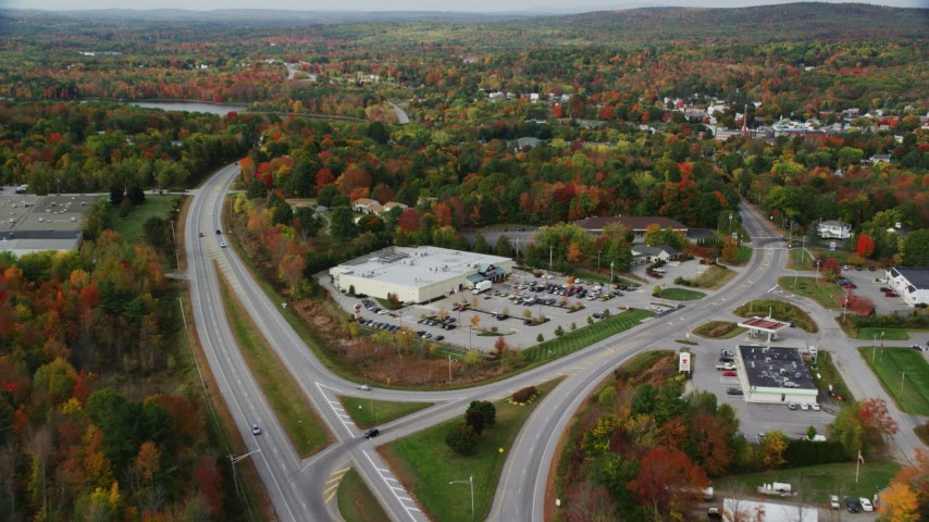 6K stock footage aerial video approaching Route 11, Hanford Supermarket, small town, autumn, Winthrop, Maine Aerial Stock Footage | AX150_013