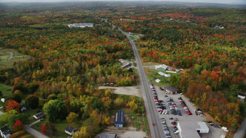 6K stock footage aerial video flying over car dealership, Route 11, colorful foliage in autumn, Winthrop, Maine Aerial Stock Footage | AX150_024