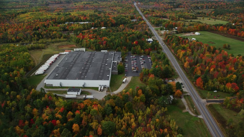 6K stock footage aerial video approaching a warehouse off Route 11, tilt down to bird's eye view, autumn, Winthrop, Maine Aerial Stock Footage | AX150_025