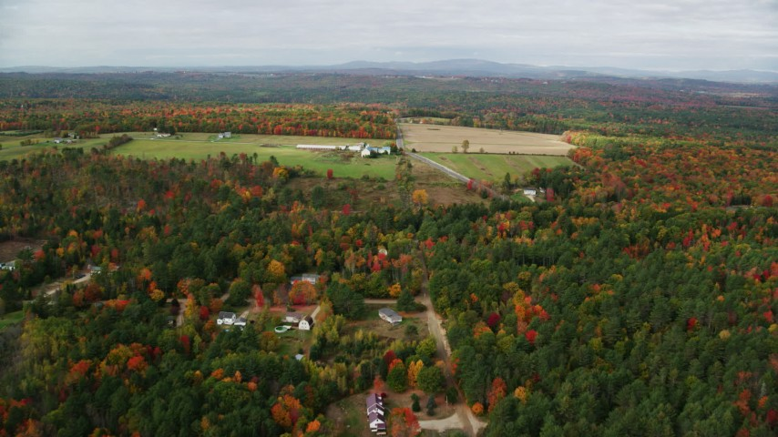 6K stock footage aerial video flying over colorful trees, approaching a farm, autumn, Leeds, Maine Aerial Stock Footage | AX150_034