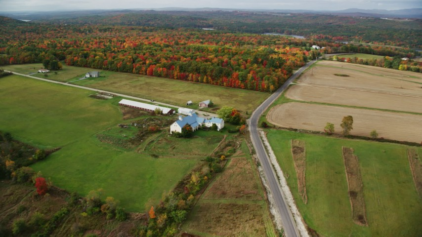 6K stock footage aerial video flying by farm, barn and rural road near colorful forest, autumn, Leeds, Maine Aerial Stock Footage | AX150_035