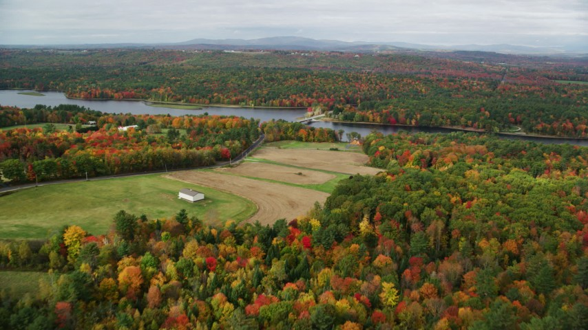 6K stock footage aerial video flying over farm, approach Center Bridge, Androscoggin River, autumn, Leeds, Maine Aerial Stock Footage | AX150_036