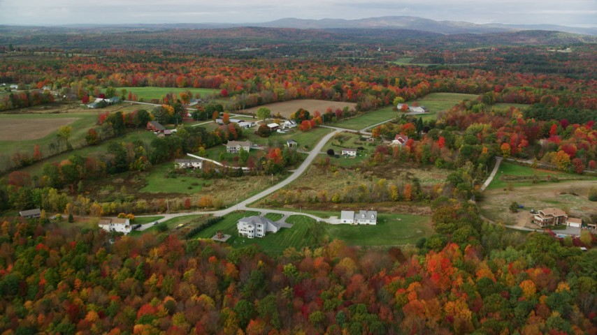 6K stock footage aerial video flying over colorful trees, approaching farm, rural homes, autumn,Turner, Maine Aerial Stock Footage | AX150_039