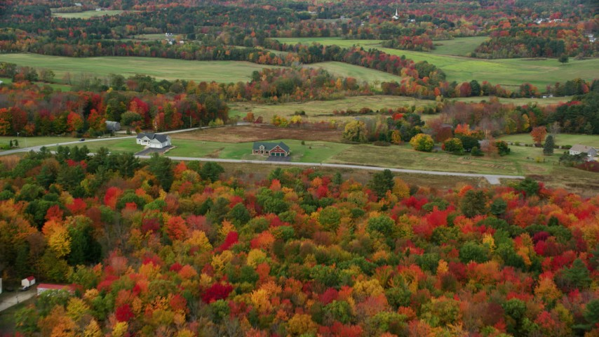 6K stock footage aerial video flying over colorful forest in autumn, approaching farms, Turner, Maine Aerial Stock Footage | AX150_040