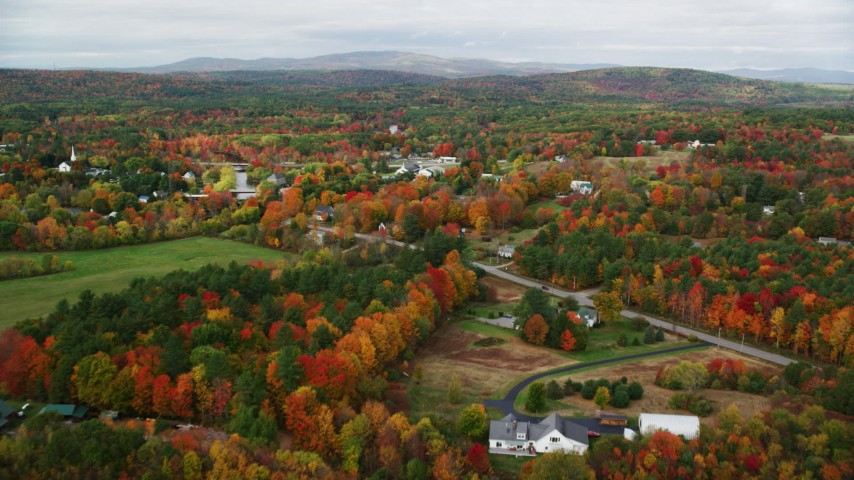6K stock footage aerial video flying by a small rural town, colorful foliage in autumn, Turner, Maine Aerial Stock Footage | AX150_042