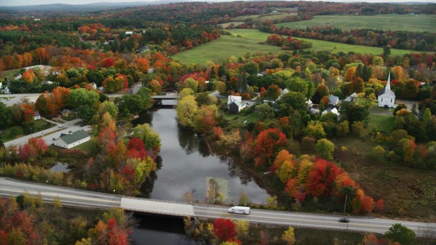 6K aerial video orbiting rural town, small bridges, Nezinscot River, autumn, Turner, Maine Aerial Stock Footage | AX150_045