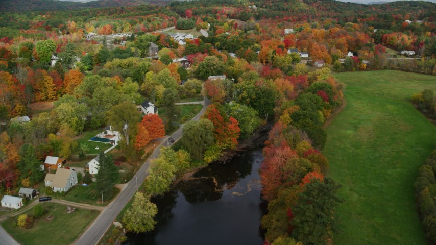 6K stock footage aerial video orbiting small rural town, colorful trees, Nezinscot River, autumn, Turner, Maine Aerial Stock Footage | AX150_048