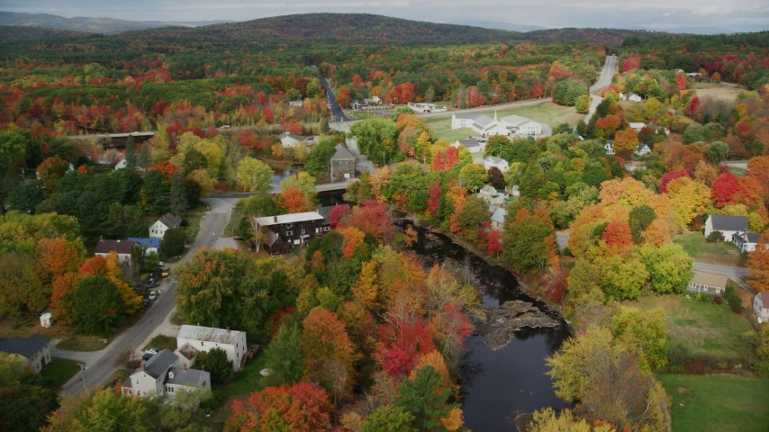 6K stock footage aerial video orbiting small rural town, bridges spanning Nezinscot River, autumn, Turner, Maine Aerial Stock Footage AX150_049