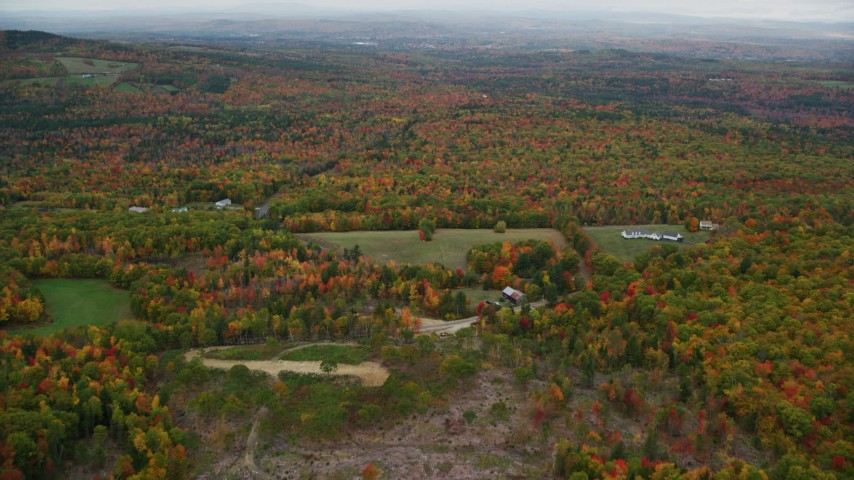 6K stock footage aerial video flying over rural homes, approaching colorful forest, autumn, Paris, Maine Aerial Stock Footage | AX150_074